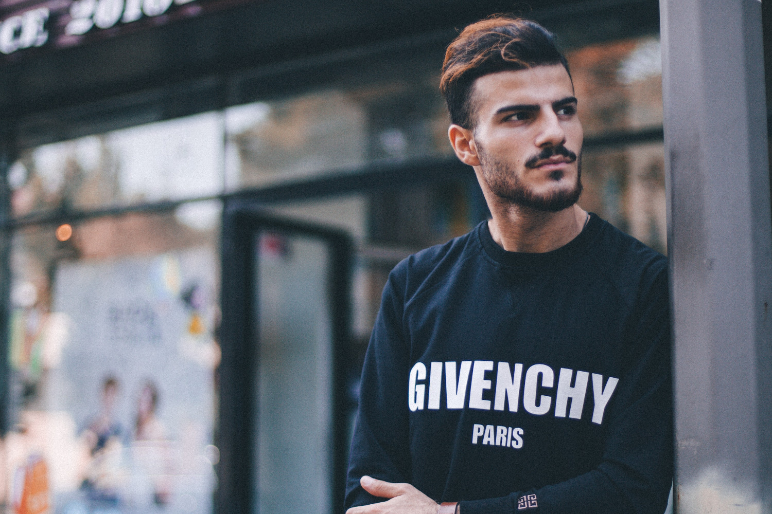 Man in black Givenchy sweatshirt standing beside of post in front of Strek store during daytime