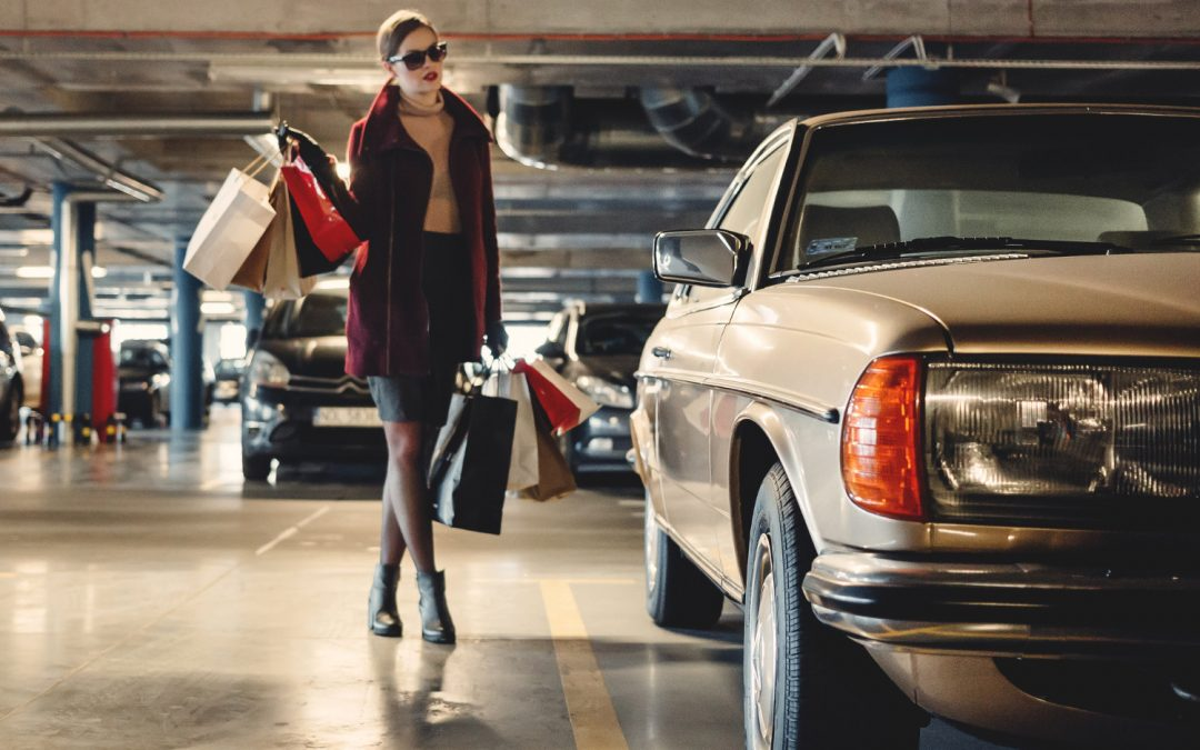 Carrying shopping paper bags walking towards beige car inside parking lot